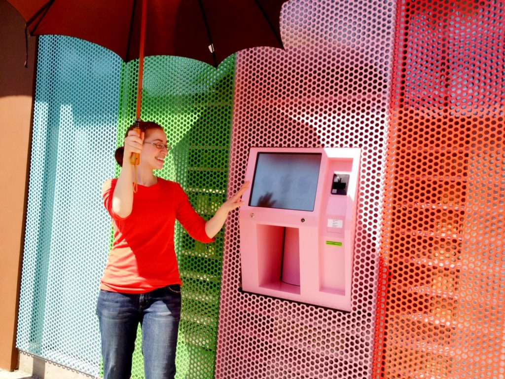 A parasol is required to keep the strong Spring sun off the screen at the Sprinkles cupcake vending machine in Beverly Hills . mobile Photography