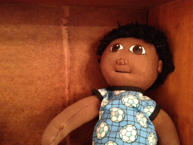This adorable South African Uthandu doll wears a dress with soccer balls on it, Kwandwe